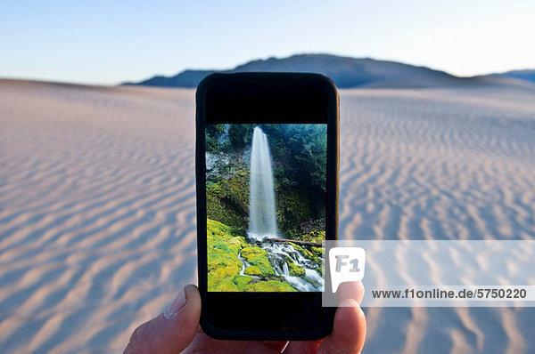 Mann hält Handy mit Wasserfallbild im Death Valley National Park  Kalifornien  USA