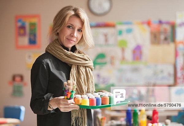 Mitte adult Woman holding malen Töpfe im Klassenzimmer Porträt
