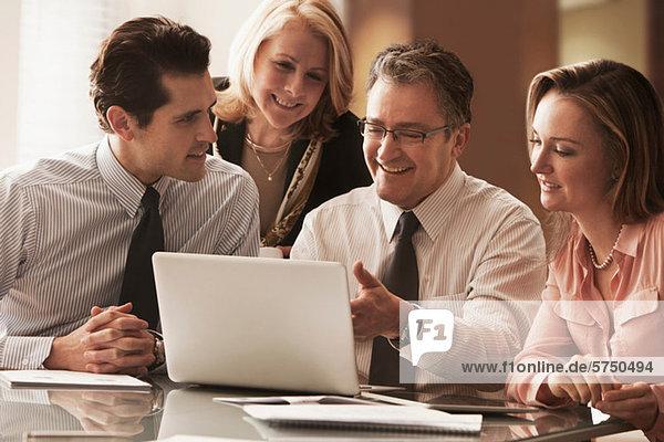 Geschäftskollegen arbeiten am Laptop auf dem Schreibtisch  lächelnd