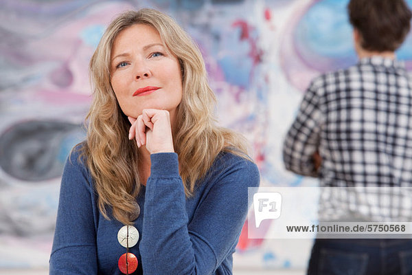 Mid adult woman sitting in front of oil painting in gallery