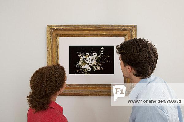 Young Couple looking at Drucken in Bilderrahmen