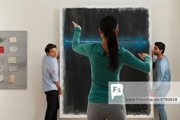 Kunsthändler beim Aufhängen von Ölgemälden in der Galerie