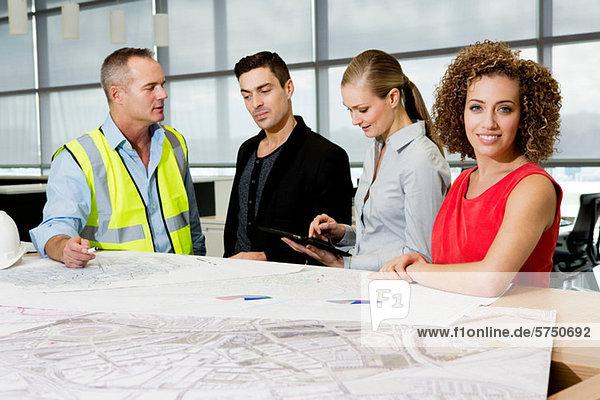Mit Blick auf Blueprints und digital Tablet im Büro Architekten Ingenieur