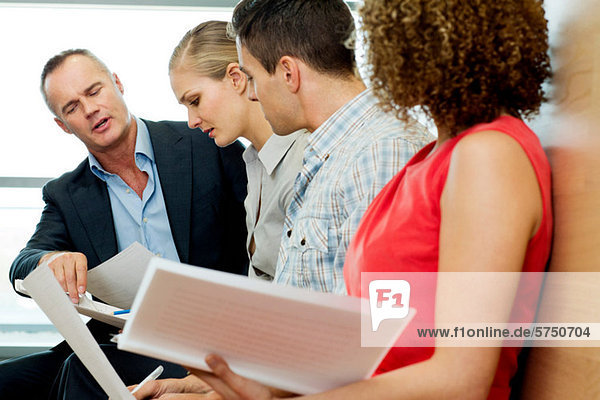 Bürokollegen beim Lesen von Dokumenten im Büro