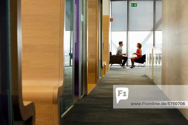 Junge Frau und Mann in der Sitzung im Büro