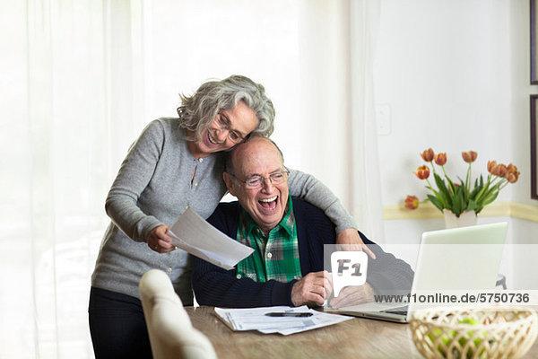 Senior Senioren benutzen Notebook lachen Wohnhaus