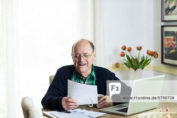Interior  zu Hause  Senior  Senioren  Mann  Schreibtisch  sehen  Dokument