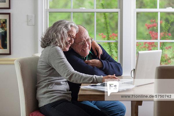 Senior Paar mit Laptop zu Hause  lachend