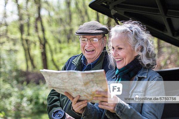 Seniorenpaar beim Lesen der Karte auf dem Kofferraum im Wald