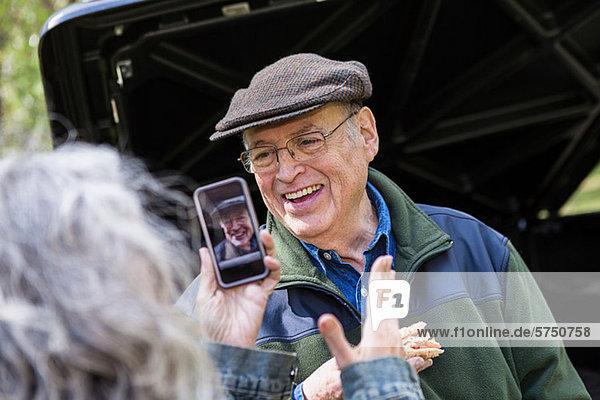 Senior Woman aufnehmen Bildmitteilung von lächelnd mann outdoors