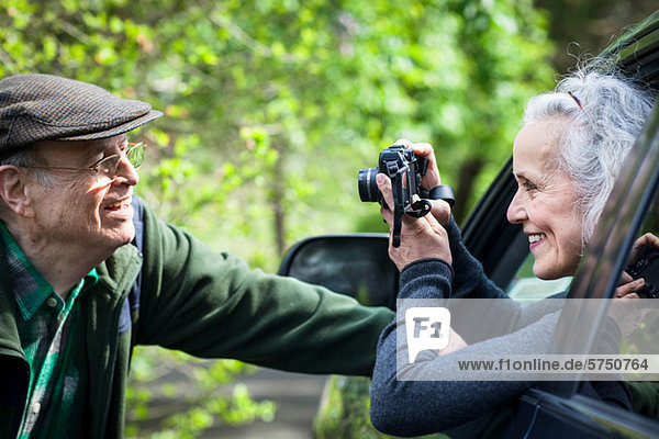 Senior woman photographing man from car