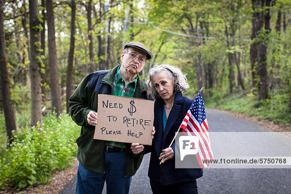 Senior Couple holding Sign in Wald  Porträt