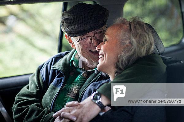 Seniorenpaar umarmt sich hinten im Auto