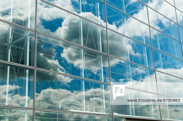 Wolkenblauer Himmel spiegelt sich in den Bürofenstern wider