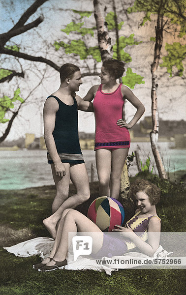 Historical picture of man with two women by a lake
