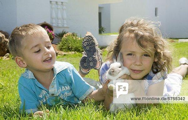 Junge und Mädchen spielen mit einem Hasen