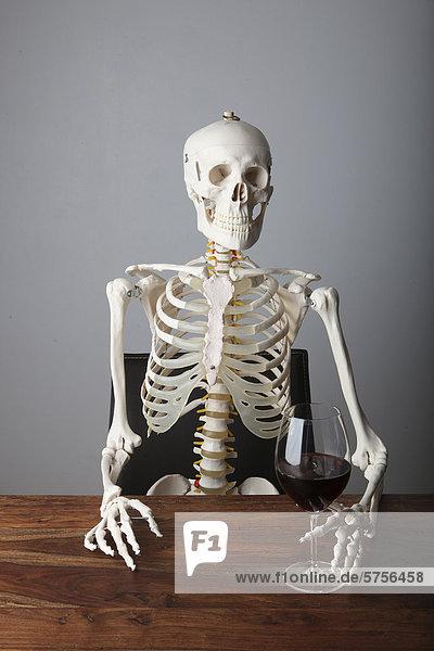 Skelett mit einem Glas Rotwein am Tisch