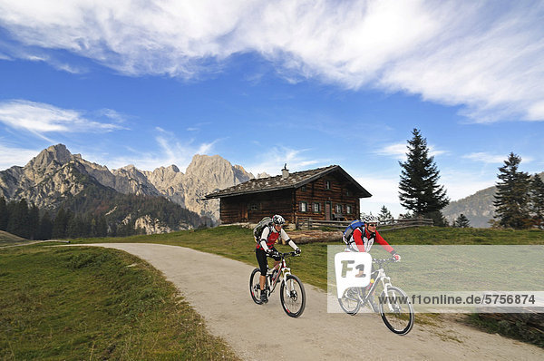 Mountain bikers cycling in front of Hochkalter mountain  as seen from Litzl-Alm alp  district of Berchtesgadener Land  Upper Bavaria  Bavaria  Germany  Europe