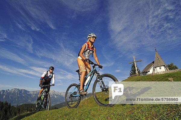 Mountainbiker auf der Kraftalm  hinten der Wilde Kaiser  Hohe Salve  Kitzbühler Alpen  Tirol  Österreich  Europa