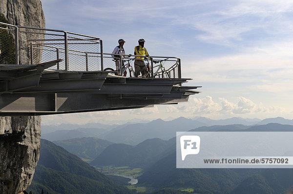 Mountainbiker auf gläserner Aussichtsplattform des Triassic Park  Steinplatte  Waidring  Tirol  Österreich  Europa