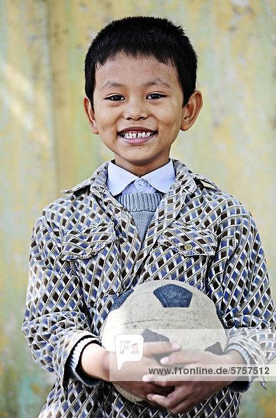 Lächelnder  asiatischer Junge mit Fußball  Portrait  Burma  Birma  Myanmar  Südostasien  Asien