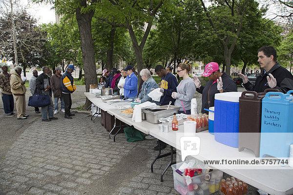 Freiwillige beten vor dem Servieren einer Mahlzeit an Obdachlose im Cass Park  die informelle Gruppe bringt alle zwei Wochen Nahrung in den Park  Detroit  Michigan  USA