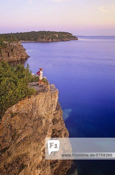Eine junge Frau Wanderer bewundert die Landschaft bei Sonnenaufgang von einem Aussichtspunkt über die Niagara-Schichtstufe entlang der Bruce Trail  Bruce Peninsula National Park  Ontario  Kanada.
