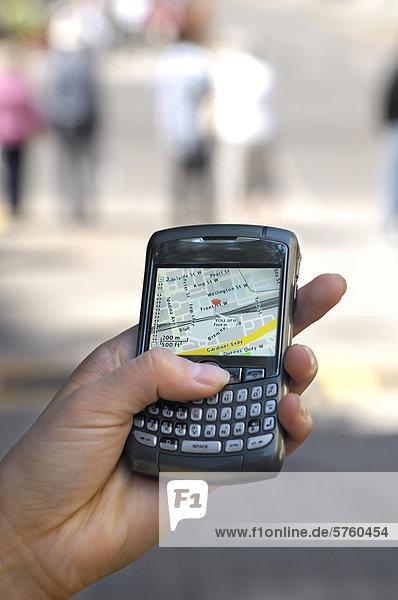 Nahaufnahme einer Person mit BlackBerry Curve 8310 Smartphone auf der Straße Anzeige GPS City Karte Ergebnis aktuelle Lage