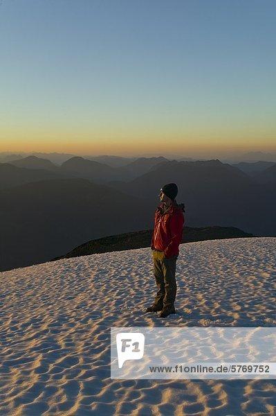 Ein einsamer Bergsteiger steht auf der Spitze des Königs Peak und genießt die letzten Strahlen der untergehenden Sonne  Strathcona Park  zentrale Vancouver Island  British Columbia  Kanada
