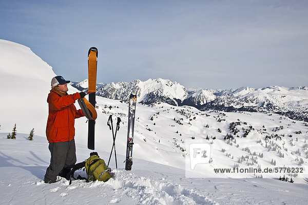 Ein junger Mann zieht aus seiner Häute und bereitet für ein Pulver-Abstieg in den Monashee Berge  Britisch-Kolumbien  Kanada