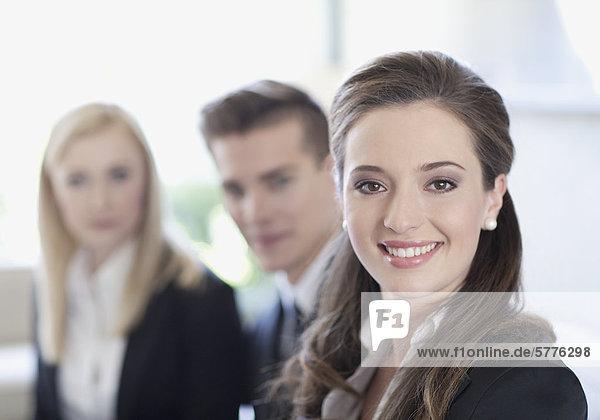 Drei Businesspersonen  junge Frau im Vordergrund