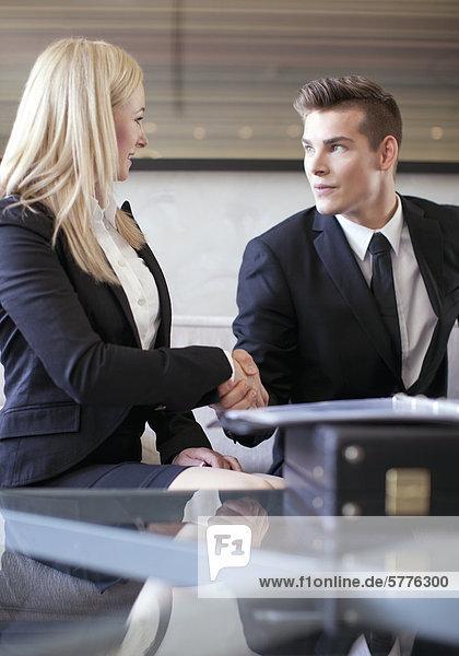 Junge Frau und junger Mann  Händedruck Junge Frau und junger Mann, Händedruck