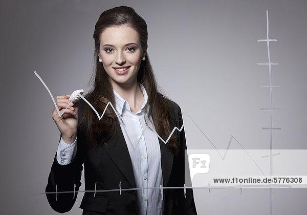 Junge Frau zeichnet Umsatzkurve Junge Frau zeichnet Umsatzkurve