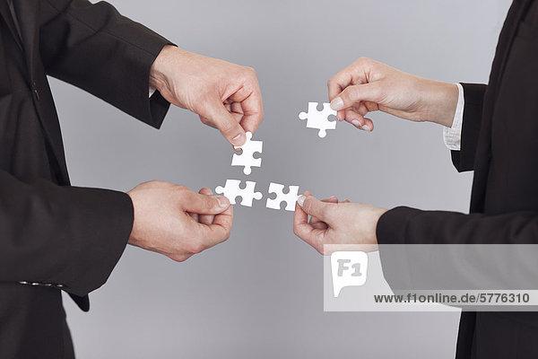 Hände mit einzelnen Puzzleteilen Hände mit einzelnen Puzzleteilen