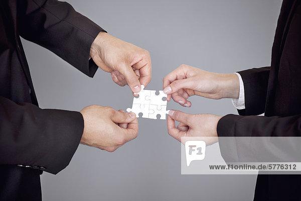 Hände fügen Puzzleteile zusammen Hände fügen Puzzleteile zusammen
