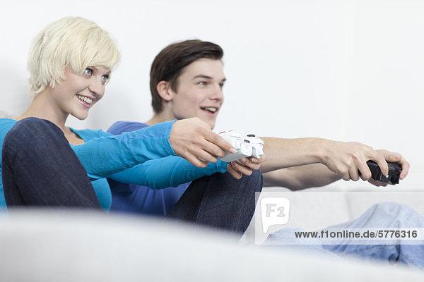 Junge Frau und junger Mann beim Computerspiel Junge Frau und junger Mann beim Computerspiel