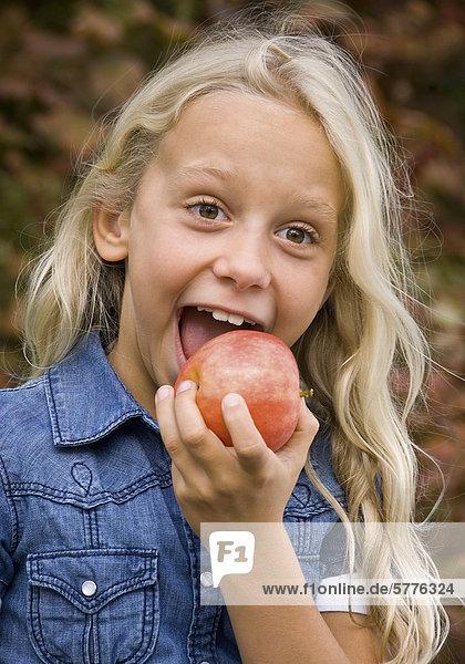 Blondes Mädchen beißt in Apfel Blondes Mädchen beißt in Apfel