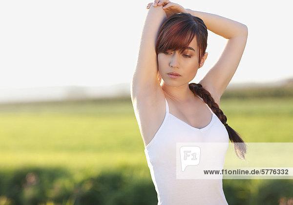 Junge Frau bei Stretching-Übung Junge Frau bei Stretching-Übung