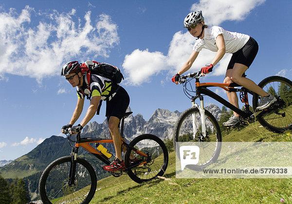 Pärchen mit Mountainbike im Gebirge Pärchen mit Mountainbike im Gebirge