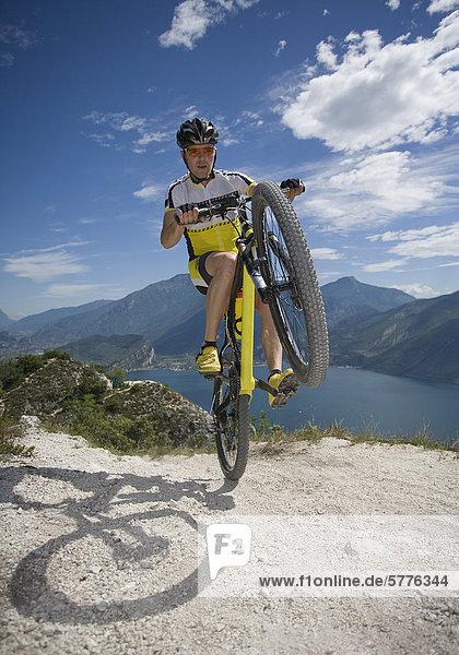 Mountainbiker fährt nur auf Hinterreifen Mountainbiker fährt nur auf Hinterreifen