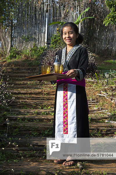 Traditionally dressed smiling waitress serving drinks  woman from the Black Hmong hill tribe  ethnic minority from East Asia  Northern Thailand  Thailand  Asia