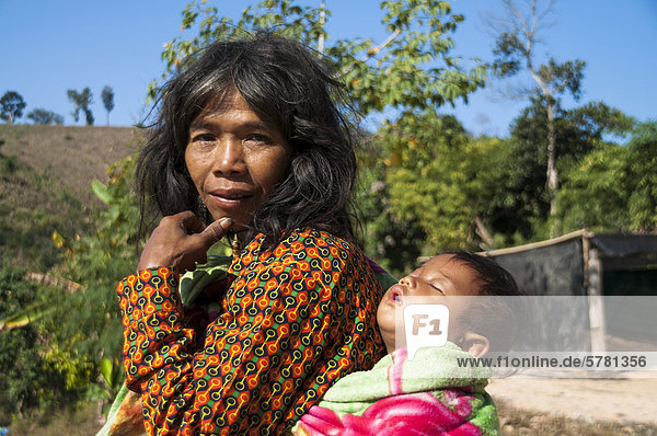 'Woman dressed with modern clothing with a child from the Mlabri  Mrabri  Yumbri  Ma Ku or ''Spirits of the Yellow Leaves'' hill tribe  ethnic minority  nomads  village  Northern Thailand  Thailand  Asia'