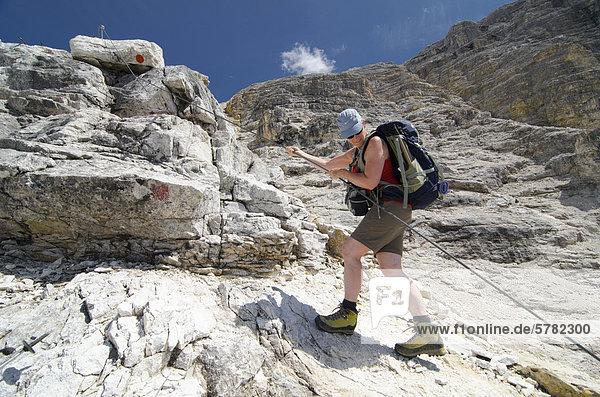 Junge Frau klettert  mit Stahlseil gesicherte Wegpassage im Schlauchkar  Naturpark Karwendelgebirge  Tirol  Österreich  Europa
