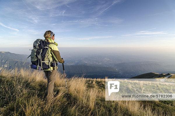 Wanderin mit Rucksack blickt vom Col Visentin in die Weite der Piave-Ebene  Italien  Europa