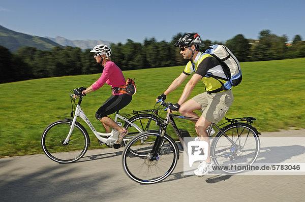 Couple cycling on electric bicycles  Reit im Winkl  Chiemgau  Upper Bavaria  Bavaria  Germany  Europe