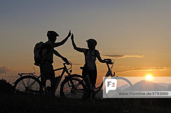 Paar mit Elektrofahrrädern auf der Winklmoos-Alm bei Sonnenuntergang  Reit im Winkl  Chiemgau  Oberbayern  Bayern  Deutschland  Europa