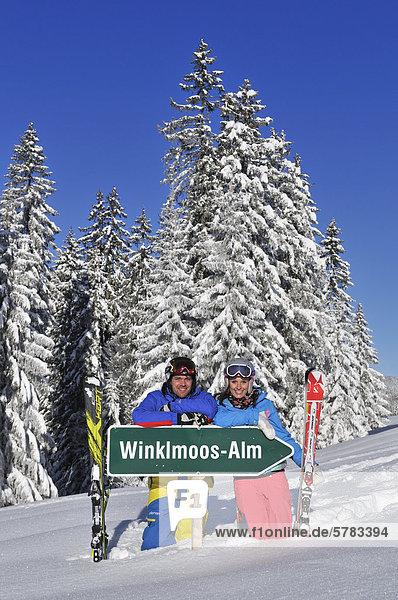 'Skiers with the sign ''Winklmoos-Alm''  Reit im Winkl  Chiemgau  Bavaria  Germany  Europe'