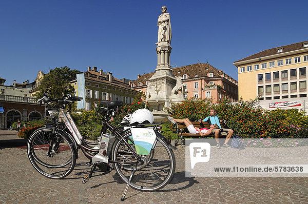 Paar mit Elektrorädern bei der Rast  Waltherplatz  Bozen  Südtirol  Italien  Europa