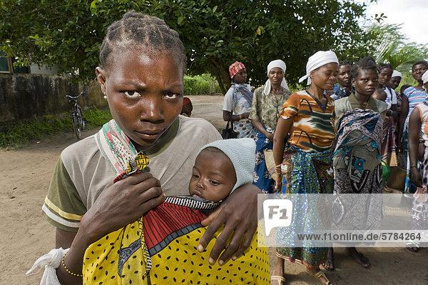 Mutter wartet mit ihrem Kind auf medizinische Behandlung vor einer HIV-AIDS-Ambulanz in Quelimane  Mosambik  Afrika