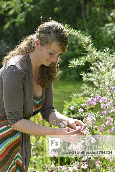 Frau betrachtet Akelei-Blüten im Garten